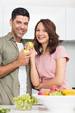Portrait of a smiling couple with fruits in kitchen