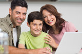 Smiling couple with son using laptop