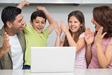 Cheerful couple with kids using laptop