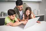 Father with kids using laptop in kitchen