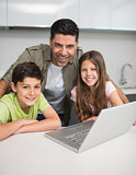 Smiling father with young kids using laptop in kitchen