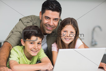 Smiling father with kids using laptop in kitchen