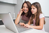 Smiling mother with daughter using laptop in kitchen