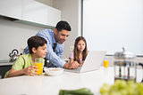 Father using laptop and kids having breakfast in kitchen