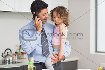 Well dressed father carrying daughter while on call in kitchen