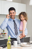Well dressed father carrying daughter while on call