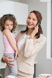 Well dressed mother carrying daughter while on call in kitchen