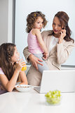 Well dressed mother with daughters and laptop in kitchen