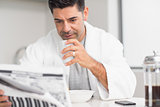 Serious man with coffee cup reading newspaper in kitchen