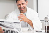 Smiling casual man with coffee cup reading newspaper in kitchen