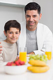 Portrait of happy son with father having breakfast