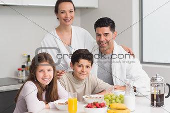 Portrait of happy kids enjoying breakfast with parents