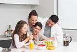 Happy kids enjoying breakfast with parents in kitchen
