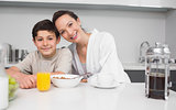 Portrait of a smiling mother with son in kitchen