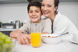Smiling mother with son at breakfast table in kitchen