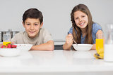 Smiling young siblings enjoying breakfast in kitchen