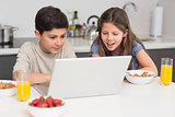 Smiling siblings enjoying breakfast while laptop in kitchen