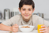 Smiling young boy enjoying breakfast in kitchen