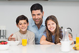 Kids enjoying breakfast with father in kitchen