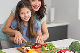 Smiling woman with daughter chopping vegetables in kitchen