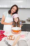 Young girl and mother preparing cookies in kitchen
