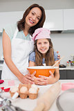 Portrait of girl and mother preparing cookies in kitchen