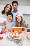 Portrait of a family of four preparing cookies in kitchen