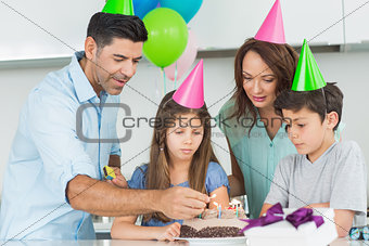 Family of four with cake at a birthday party