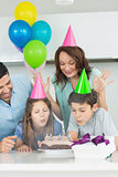 Family of four blowing cake