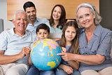 Extended family sitting on sofa with globe in living room