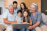 Extended family using laptop on sofa in living room
