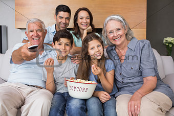 Portrait of happy extended family watching tv in living room