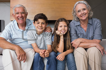 Portrait of grandparents and two kids in living room