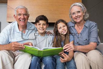 Portrait of grandparents and grandkids looking at album photo