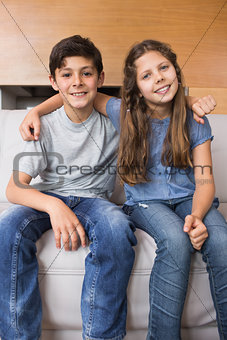 Portrait of smiling little siblings sitting in living room