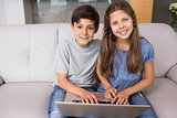 Portrait of young siblings using laptop in the living room