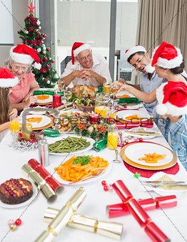 Happy family in santas hats enjoying Christmas dinner