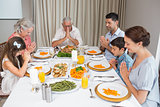 Family of six saying grace before meal at dining table