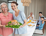Woman and grandmother holding chicken roast with family at dining table