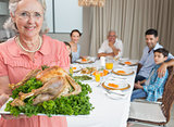 Grandmother holding chicken roast with family at dining table