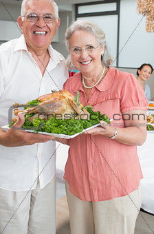 Portrait of senior couple holding chicken roast
