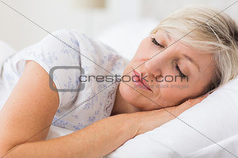 Woman sleeping with eyes closed in bed