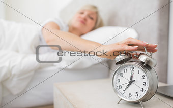 Woman extending hand to alarm clock in bed