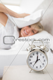 Woman covering ears with pillow with alarm clock in foreground