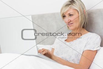 Mature woman using laptop in bed