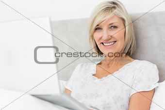 Smiling mature woman using laptop in bed