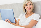 Smiling mature woman using digital tablet in bed