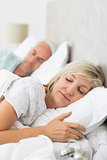 Mature couple sleeping with eyes closed in the bed