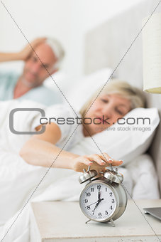 Mature woman extending hand to alarm clock in bed