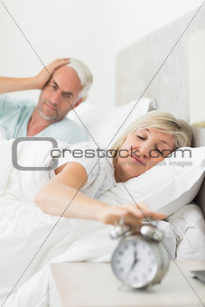 Man covering ears while woman extending hand to alarm clock in bed